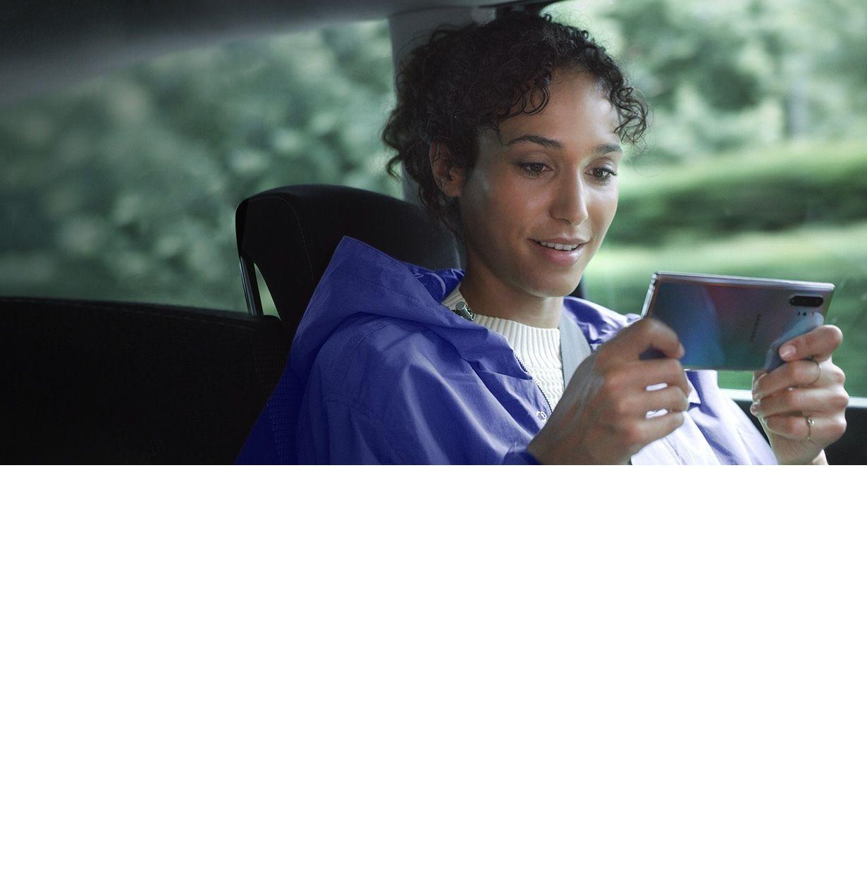 یک زن، نشسته در یک ماشین، در حالیکه یک Galaxy Note10 plus را به حالت افقی در دست گرفته است. اعلان برنامه مدیریت دانلود نشان میدهد که به لطف توانایی سریع انتقال داده سه فایل حجیم با سرعت در حال دانلود شدن هستند.